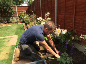 Julian planting flowers for one of his many happy clients